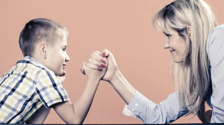 Family, children and motherhood concept. Son confronts his middle aged mother. Woman and little boy arm wrestling having fun. photo