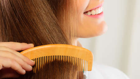 comb: Health beauty and haircare concept - Closeup young business woman refreshing her hairstyle she combing her long brown hair with wooden comb