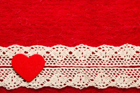 Valentines day or wedding concept. Wooden decorative heart lace ribbon on abstract red cloth background. Border frame. photo