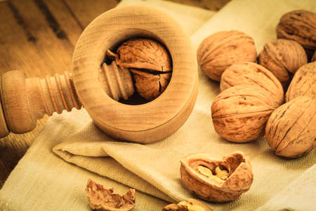 omega3: Healthy food full of omega-3 fatty acids, organic nutrition. Walnut with nutcracker on rustic old table Stock Photo