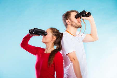 personas: Hombre y mujer j�venes socorristas de guardia o pareja de turistas que buscan a trav�s de binoculares foto de estudio en azul Foto de archivo