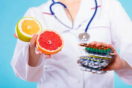 vitamins pills: Health and balanced diet concept. Choice between two sources of vitamins - pills or fruits. Medical doctor offering chemical and natural vitamins, holding stack of drugs and grapefruits on blue.
