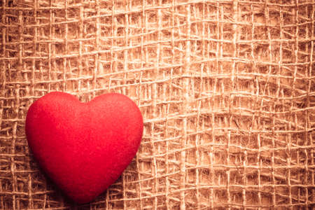 bagging: Valentines day or wedding concept. Red big heart love symbol on rustic brown bagging cloth background with copy space. Vintage aged style Stock Photo