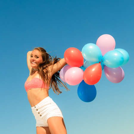 happy teens: Summer holidays, celebration and happiness concept - attractive athletic woman teen girl jumping with colorful balloons hair blowing on wind outdoors sunny day, blue sky background Stock Photo