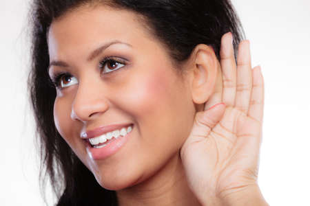 blab: Female hand to ear listening. Gossip teen girl mixed race with palm behind ear spying. Young woman listening secret.