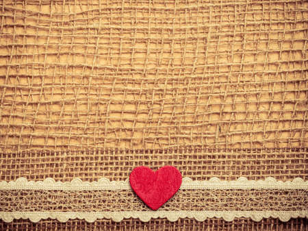 Valentines day or wedding concept. Red wooden decorative heart lace ribbon on abstract cloth burlap background with copy space. Vintage aged tone photo