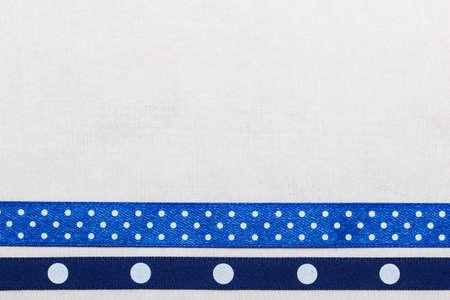 bordered: Festive celebration party frame. Polka dot navy blue satin ribbon on white cloth background Stock Photo