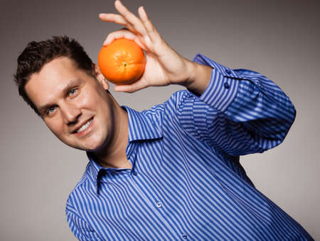 recommending: Diet and nutrition. Young smiling man holding orange tropical fruit on gray. Happy guy recommending healthy food. Stock Photo
