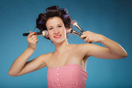 rollers: Cosmetic beauty procedures and makeover concept. Woman in hair rollers holding makeup brushes set on blue Stock Photo