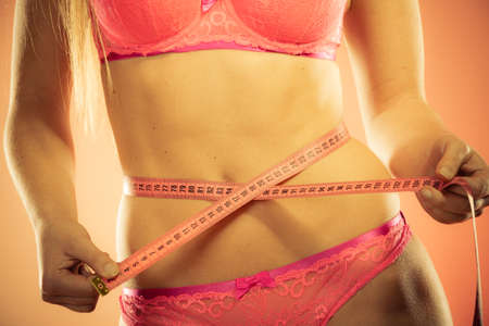 losing control: Weight loss, healthy lifestyle concept. Closeup measuring tape on woman body, fit girl wearing pink lace lingerie measuring her waistline