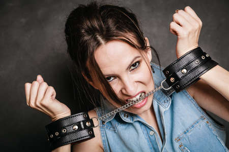 manacles: Arrest and jail. Criminal angry woman prisoner girl showing leather handcuffs on gray. Punishment. Stock Photo