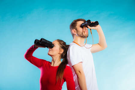 Young man and woman lifeguards on duty or tourist couple looking through binocular studio shot on blue photo