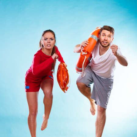 rescued: Accident prevention and water rescue. man and woman lifeguard couple on duty running with with life belt lifesaver equipment on blue