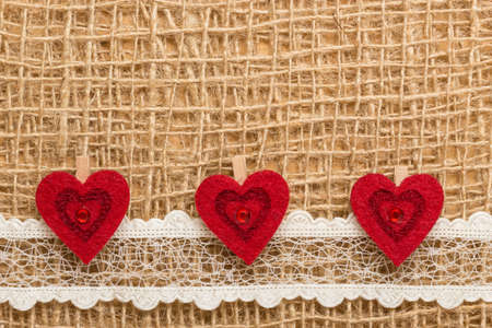 Valentines day or wedding concept. Red decorative hearts lace ribbon on rustic linen cloth background with copy space. Vintage aged style photo