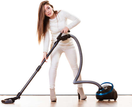 Woman vacuuming the house. Funny girl with vacuum cleaner. Housework photo