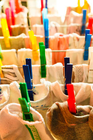 clothes clips: Housework concept. Closeup clothes hanging to dry on a laundry line with colorful pegs clips indoor