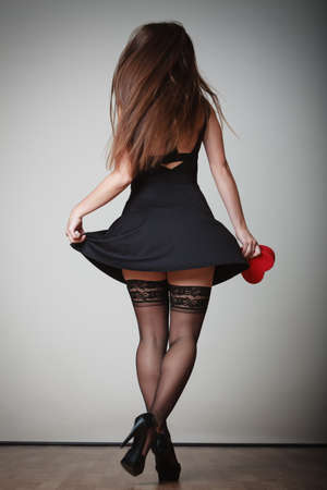 Sexy woman in dance. Girl in black dress stockings and high heels dancing, holding red heart shaped gift box. Party.