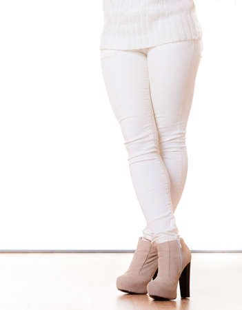 white pants: Winter fashion. Female legsin white pants foots in stylish fashionable shoes boots. Studio shot isolated