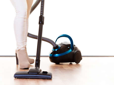 Woman vacuuming the house, female legs with vacuum cleaner. Housework photo