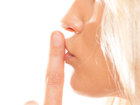 secrecy: Woman asking for silence or secrecy with finger on lips hush hand gesture. Isolated