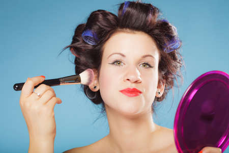 makeover: Cosmetic beauty procedures and makeover concept. Woman in hair curlers applying makeup blusher with brush. Girl gets blush on cheekbones, on blue