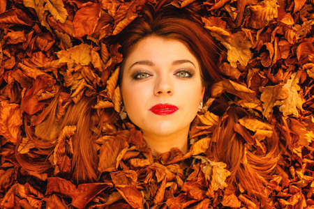 Ecology earth, eco friendly and love nature concept. Portrait young redhaired woman cover in autumn orange leaves. photo