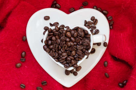 love pic: Heart shaped white cup filled with roasted coffee beans on red cloth background
