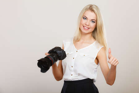 Photographer girl shooting images. Attractive blonde happy woman taking photos with camera making thumb up hand gesture, on gray photo
