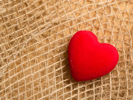 bagging: Red big heart love symbol on rustic brown bagging cloth background with copy space. Stock Photo