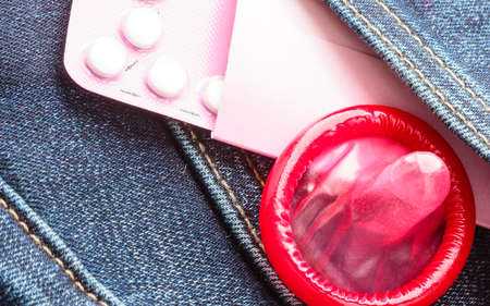 red condom: Closeup oral contraceptive pills, red condom on denim pocket background