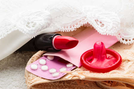 hormone  male: Closeup oral contraceptive pills, condom and red lipstick on lace lingerie. Stock Photo
