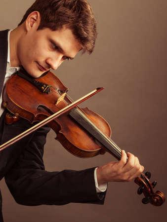 fiddler: Art and artist. Young elegant man violinist fiddler playing violin on brown. Classical music. Studio shot.