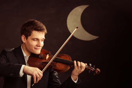 fiddler: Art and artist. Young elegant in love man violinist fiddler playing violin at moon night. Classical music. Studio shot.