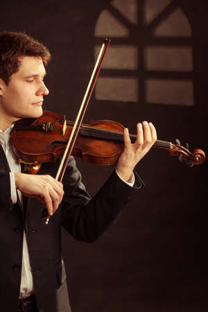 fiddler: Art and artist. Young elegant in love man violinist fiddler playing violin under the window at night. Classical music. Studio shot.