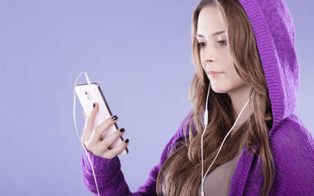 smartphones: young woman with smart phone listening music. Teen stylish long hair girl in hood relaxing or learning language. Studio shot on violet.