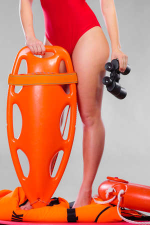 observant: Accident prevention and water rescue. Attractive female model in lifeguard outfit on duty with binocular keeping float lifesaver equipment on gray Stock Photo