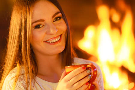 home heating: Winter at home, heating. Closeup woman face, smiling long hair girl relaxing warming up at fire fireplace, holding mug with hot drink. Indoor.