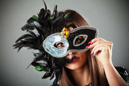 Carnival night life. Attractive woman face with hand holding mysterious mask on grey background in studio. photo