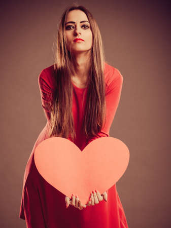 Valentines Day. Woman holding heart sign in studio. Retro vintage photo photo