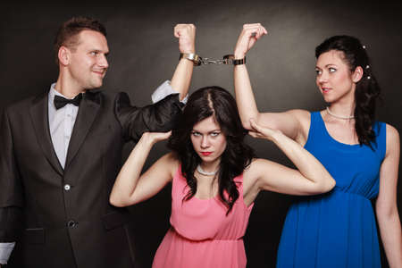 Marital infidelity concept. Love triangle two women one man passion of love hate. Mistress betrayal within the family. Black background. photo