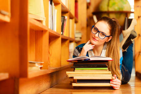 Education highschool concept. Female student charming long hair girl blue glasses working in college library with stack books. Indoor photo