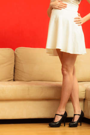 tacones rojos: Nuevo concepto de vida. El embarazo, la maternidad y la elegancia. barriga de la mujer embarazada con un vestido blanco con estilo y piernas delgadas largas en tacones altos en el hogar
