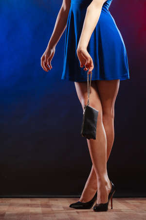 Celebration disco and evening fashion concept - woman in blue dress holding handbag bag, dancing in the club, part of body female legs in high heels on party floor photo