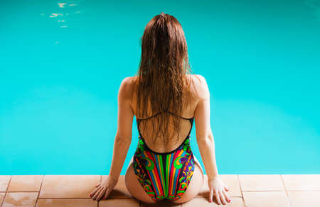 Summer time, relax and vacation concept. Sensual woman buttocks in swimsuit back view. Beautiful fit female body, girl sitting at poolside. photo