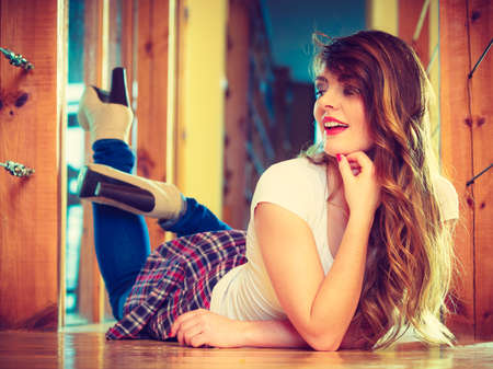 Fashion and young people concept - Full length teen girl long curly hair in denim trousers casual style relaxing at home, lying on floor photo