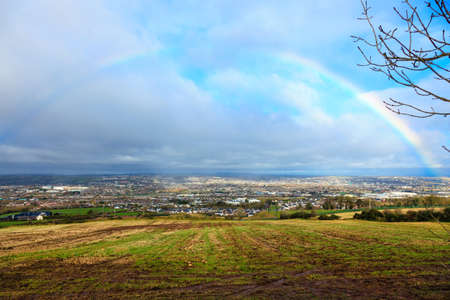 colorful cloudscape: View of town Cork, County Cork, Ireland Europe. Cloudscape with colorful rainbow over autumn city, beautiful colors phenomenon in blue sky, overcast weather, nature landscape