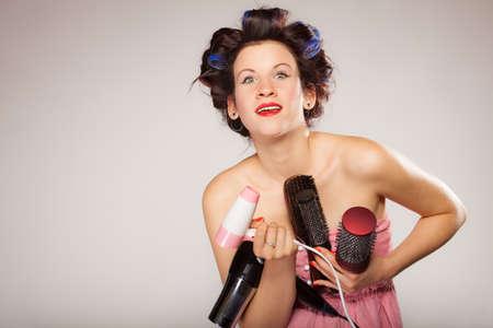 secador de pelo: Mujer joven que se prepara para la fecha que se divierten, linda chica con rulos para peinar el cabello con hairdreyer muchos accesorios cepillo peine en gris