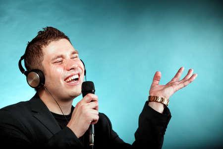 signer: Young man singing into microphone. Happy karaoke signer studio shot blue background Stock Photo