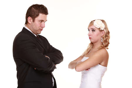 sullenly: Wedding couple conflict, bad relationships. Woman bride and man groom looking at each other with angry expression. Isolated on white