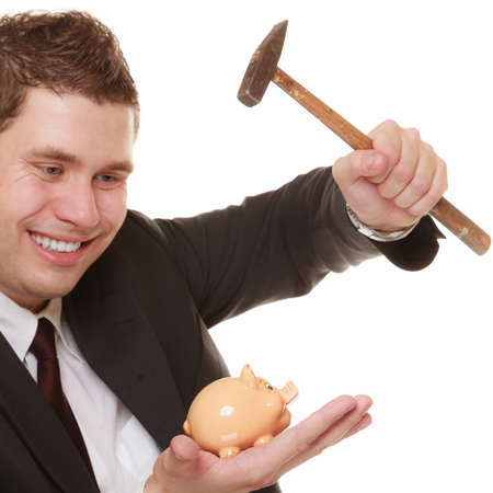 money saving concept. Happy funny business man guy with hammer about to smash piggy bank isolated on white photo